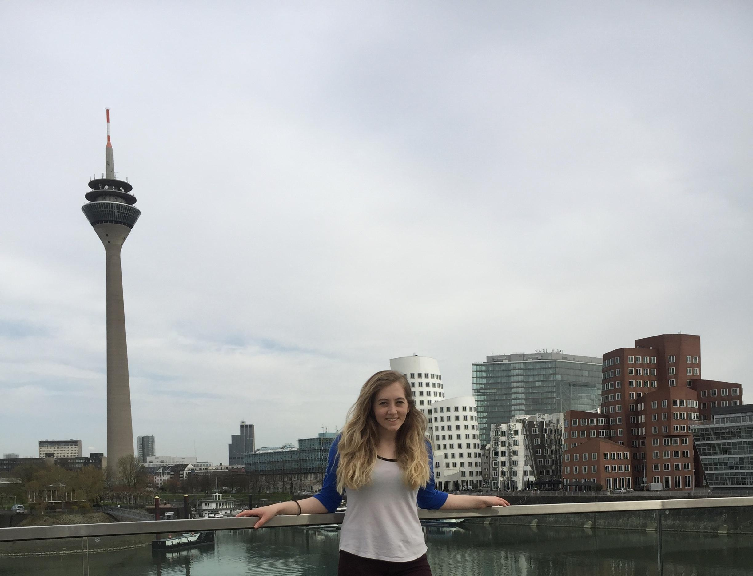 Morris Alum and Fulbright Scholar, Olivia Ilgar standing in front of the Dusseldorf, Germany skyline.