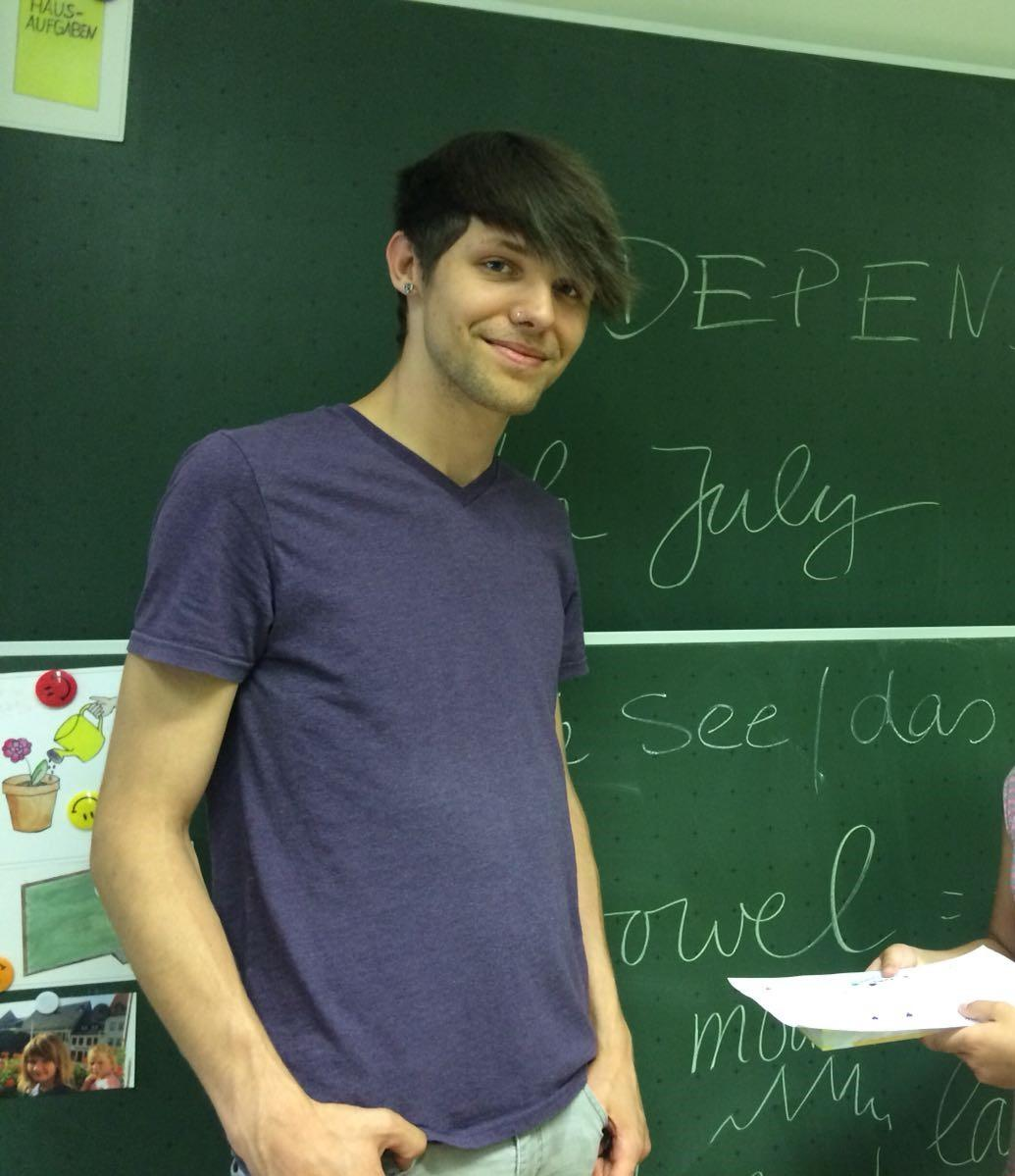 Student standing in front of a chalk board