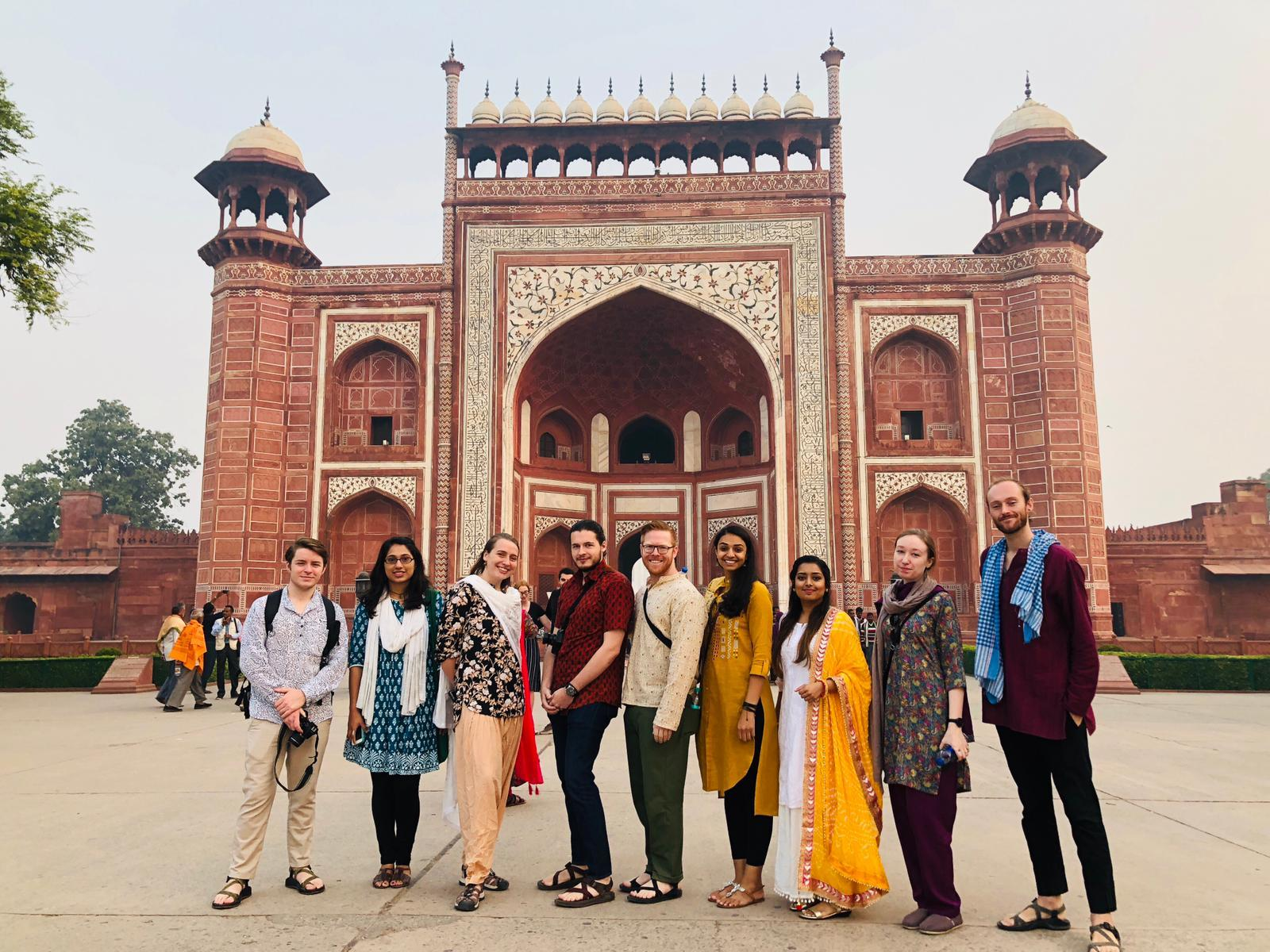 A group of diverse students in traditional Indian dress standing in front of an ancient red and white building building